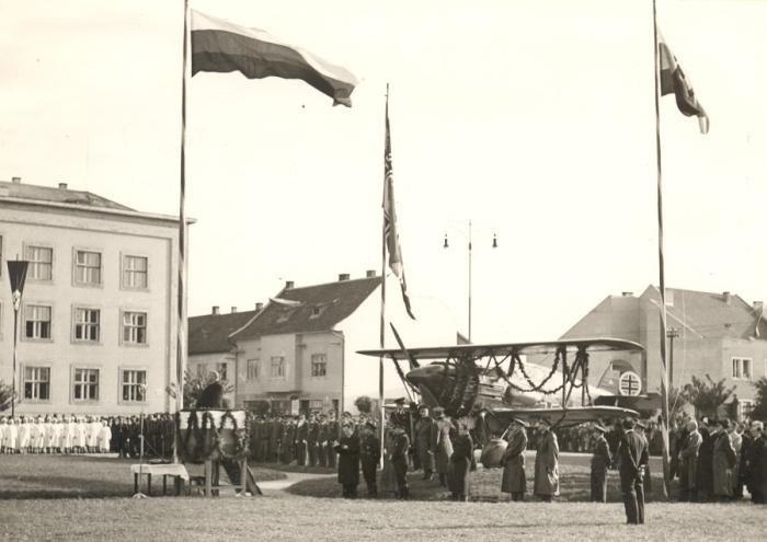 Slávnosť leteckého pluku na námestí v Piešťanoch spojená s vyznamenávaním pilotov za ťaženie proti Poľsku v roku 1939. Na tribúne reční prezident Jozef Tiso, kulisu tvorí stíhacie lietadlo Avia B-534